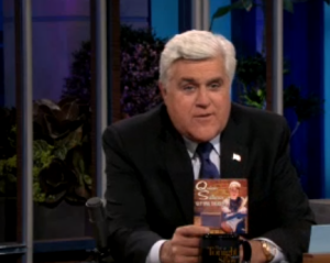Jay Leno holding up Getting There by Quinn Sullivan